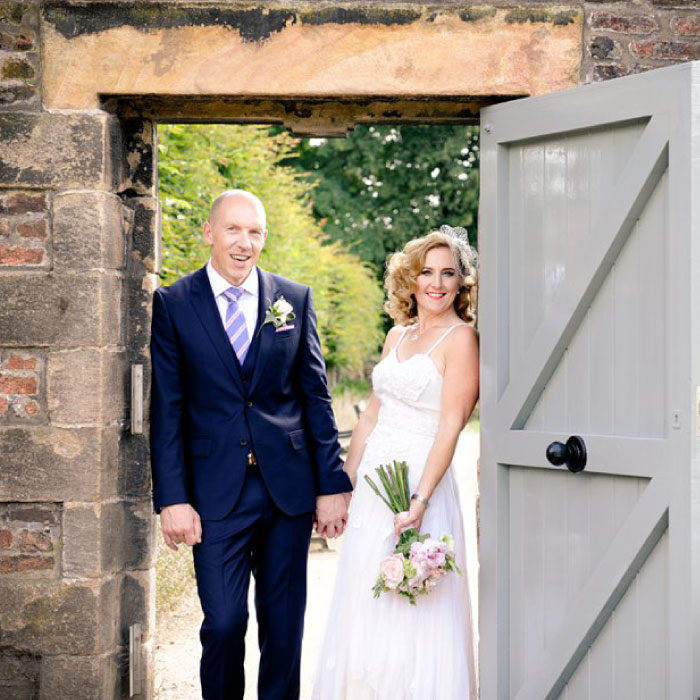 Couple posing on wedding day in traditional doorway
