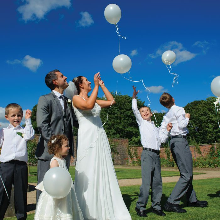 Couple with children releasing balloons into the air heading for the bright blue sky
