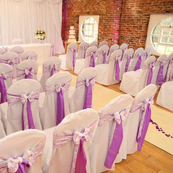 Chairs with purple bows prepared in the coach house before the wedding