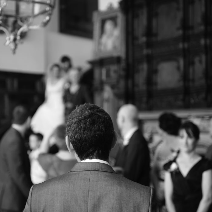 Black and white photo of wedding guests with couple burred in the background
