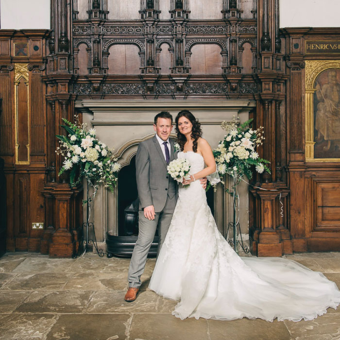 Couple posing on wedding day in front of fireplace in the hall