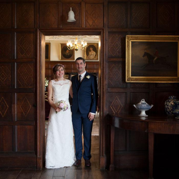 Happy couple on wedding day posing in doorway inside Astley Hall