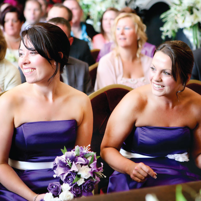Two smiling bridesmaids in purple dresses, one holding a bouquet of purple flowers